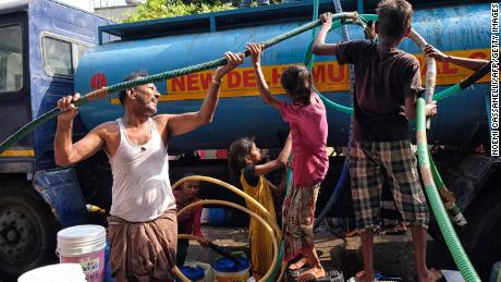 Indian residents use hoses to collect drinking water from a tanker in Sanjay, New Delhi.