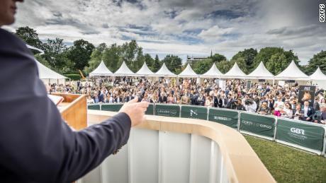 An auctioneer encourages guests to bid amid a garden party atmosphere.