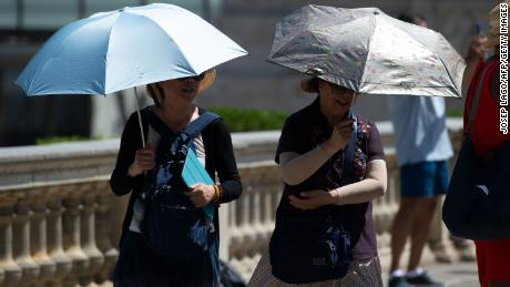 Tourists walk under umbrellas to protect themselves from the sun on a warm summer day in Barcelona on June 28.
