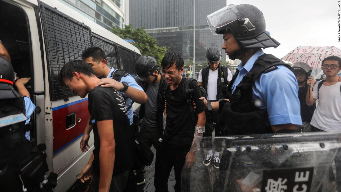 Police detain protesters near the government headquarters in Hong Kong on July 1.