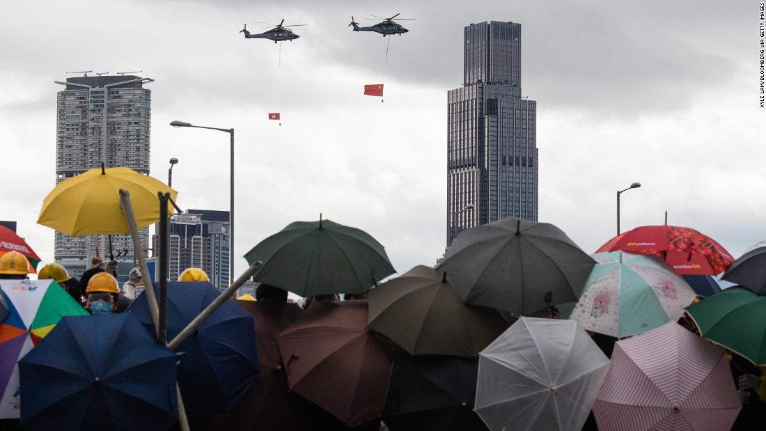 Helicopters carrying the flags of China and Hong Kong fly over demonstrators on July 1.