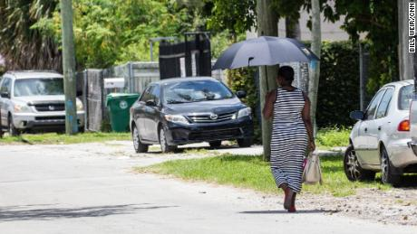 A woman uses an umbrella for shade as she walks on a hot day in Miami.