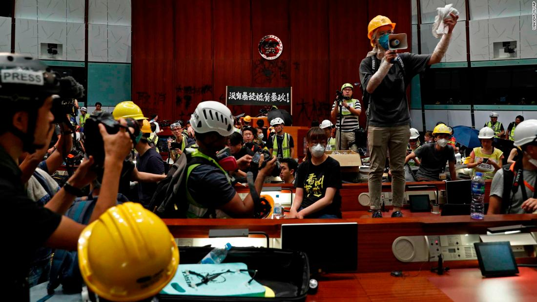A protester uses a megaphone to speak to other protesters inside the Legislative Council building.