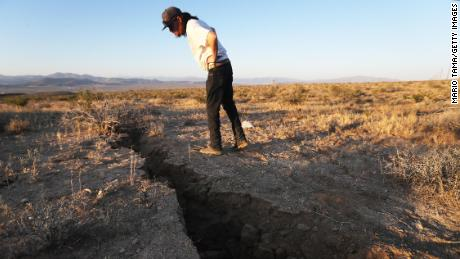 A resident inspects a crack in the earth after a 6.4 magnitude earthquake struck on July 4 near Ridgecrest, California.