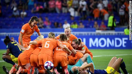 Netherlands players pile on top of each other after victory over Sweden.