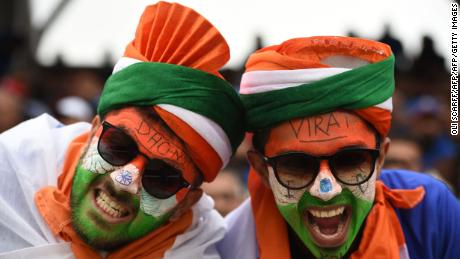 Indian supporters with faces painted in the national colours pose for a photograph.