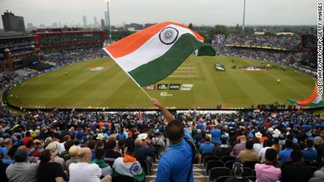 An Indian supporter waves the national flag high up in the stands as the teams come out.
