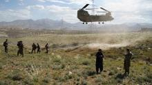 In this photo taken on June 6, 2019, a US military Chinook helicopter lands on a field outside the governor's palace during a visit by the commander of US and NATO forces in Afghanistan, General Scott Miller, and Asadullah Khalid, acting minister of defense of Afghanistan, in Maidan Shar, capital of Wardak province.