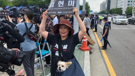 """A protester against the dog meat trade holds up a sign reading """"Bystander of Dog Slaughter, MP Kim Hyun-mee"""" outside South Korea's National Assembly."""