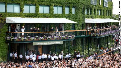 Novak Djokovic lifts the trophy as a crowd assembles at Wimbledon.
