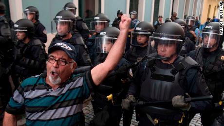 La policía impide que los manifestantes avancen a la residencia del gobernador de La Fortaleza en San Juan el domingo.