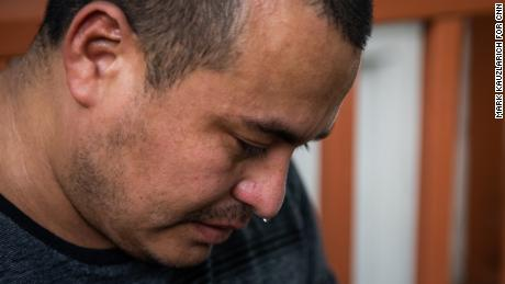 Manuel Gámez cries while looking at photos of his daughter.