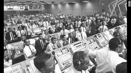 Members of the Kennedy Space Center state industry team are rising from their consoles within the Launch Control Center to lift the Apollo 11 by lifting a window.