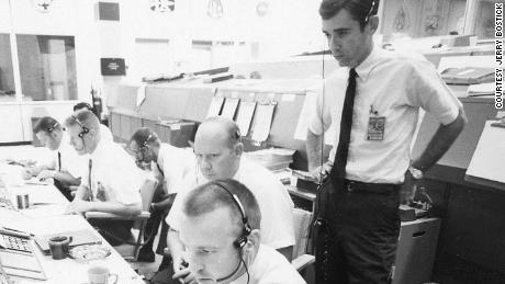 The Apollo 11 flight dynamics team includes Jerry Bostick, seen standing behind Philip Shaffer and David Reed.