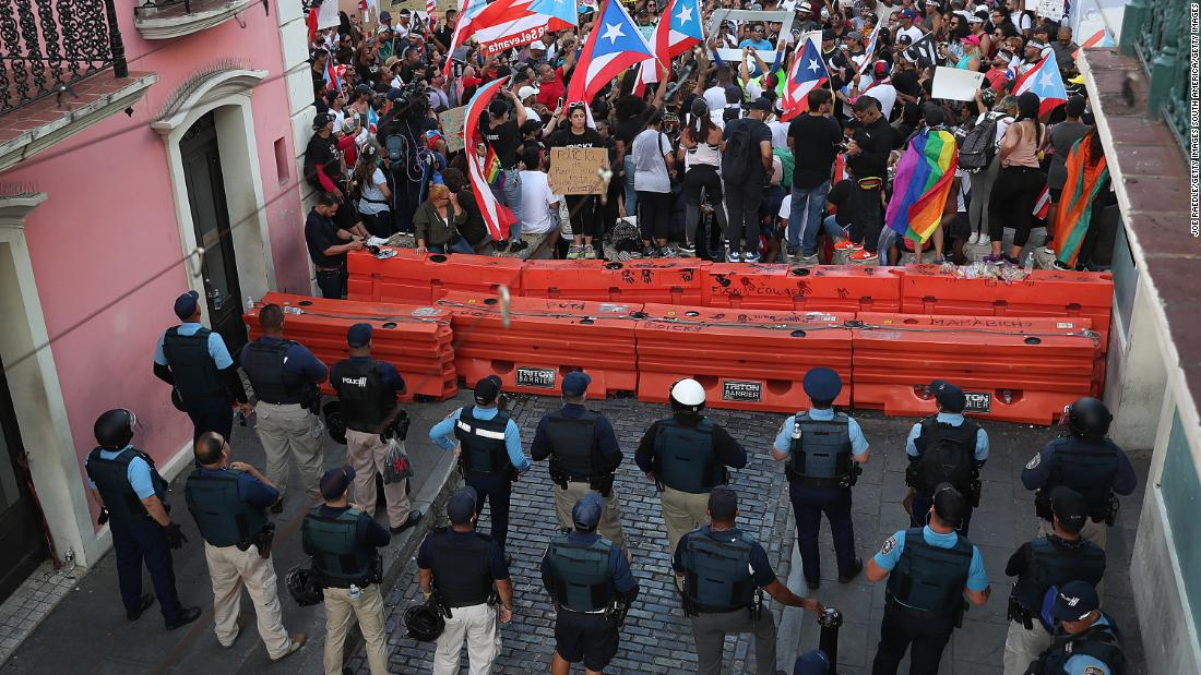 A police barricade blocks protesters on a San Juan street leading to the governor's mansion on Saturday, July 20.