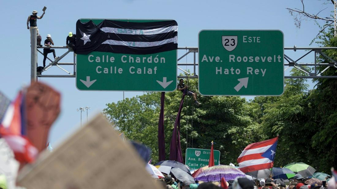 People protest on a highway sign on Monday.