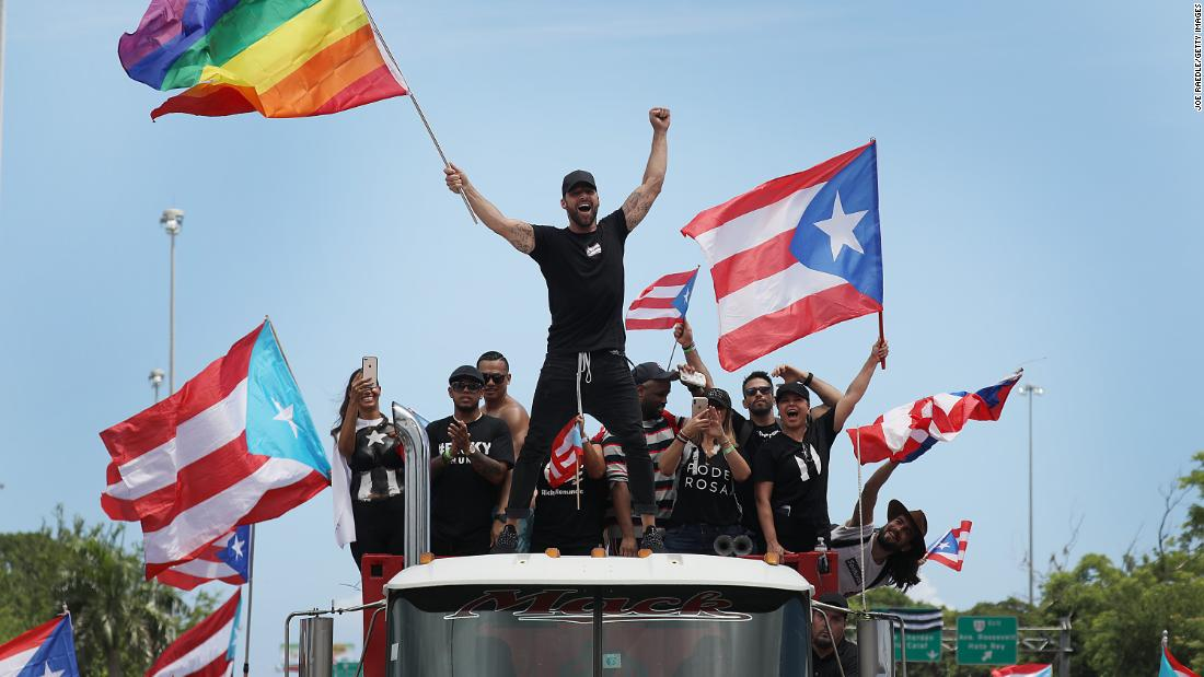 Puerto Rican pop star Ricky Martin, waving a rainbow flag, joins the protests on Monday. Martin was personally attacked in the chats that Rosselló took part in. Members of the group chat made vulgar references to the star's sexuality.