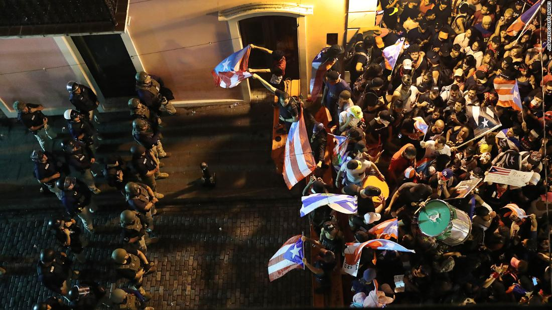 Protesters demonstrate near a police  barricade set up along a street leading to the governor's mansion on Monday, July 22, in San Juan, Puerto Rico.