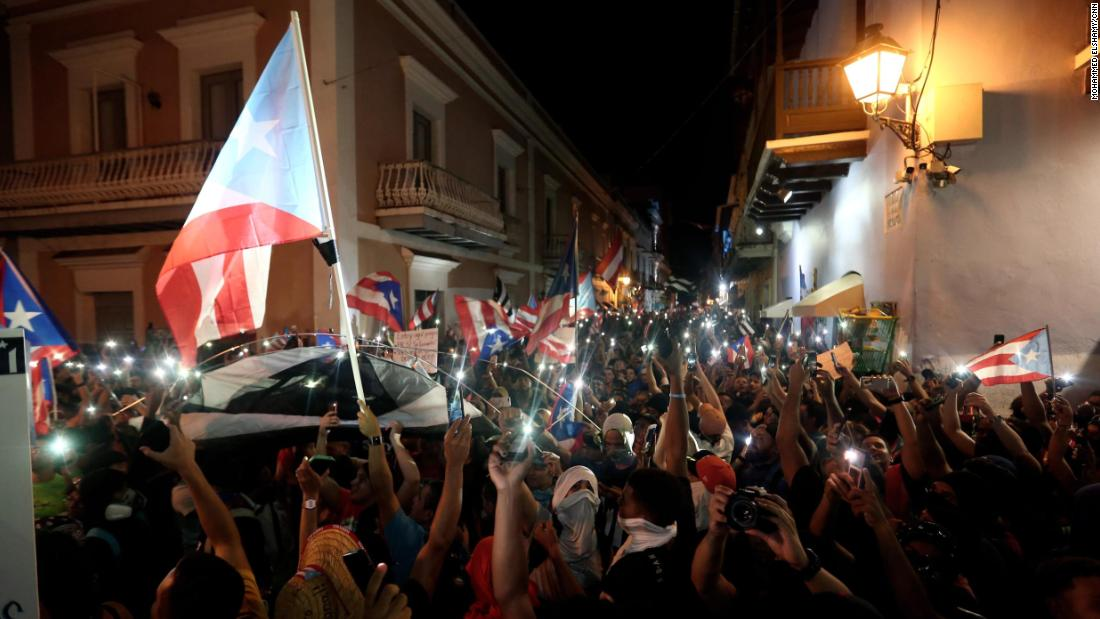 People hold up their phones during a rally in front of La Fortaleza in old San Juan.