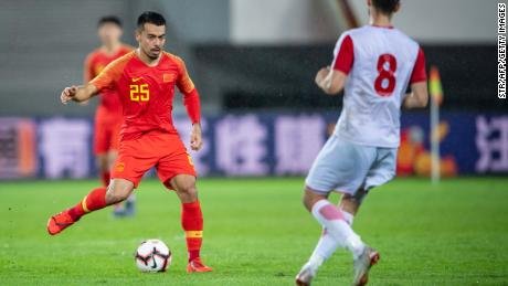China's Nico Yennaris (L), known as Li Ke in Chinese, is challenged by Muhammadjon Rahimov of Tajikistan during a friendly in Guangzhou.