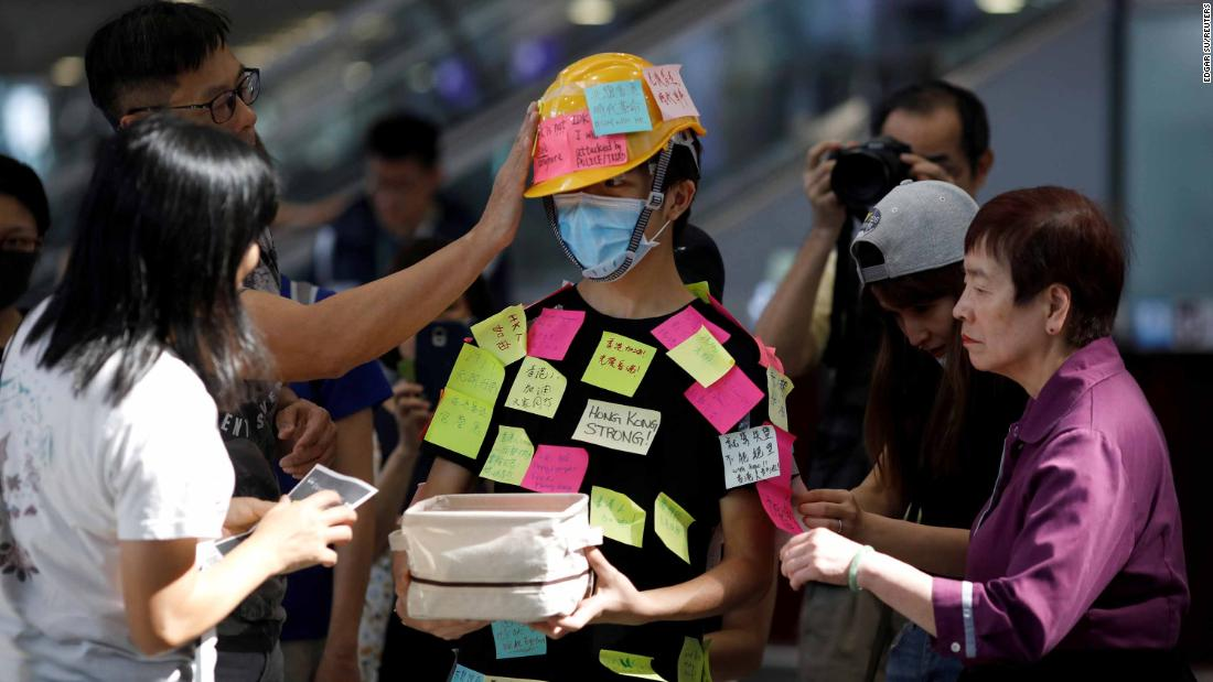 People paste Post-it notes on a demonstrator in the Hong Kong airport.