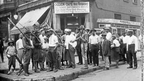 In this 1919 photo provided by Chicago History Museum, a crowd of men and armed National Guard stand in front of the Ogden Cafe during race riots in Chicago.