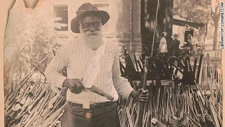 In this July 13, 1919 image provided by the Library of Congress, Daniel Hoskins stands with guns deposited at Gregg County Courthouse, in Longview, Texas, following race riots during Red Summer.