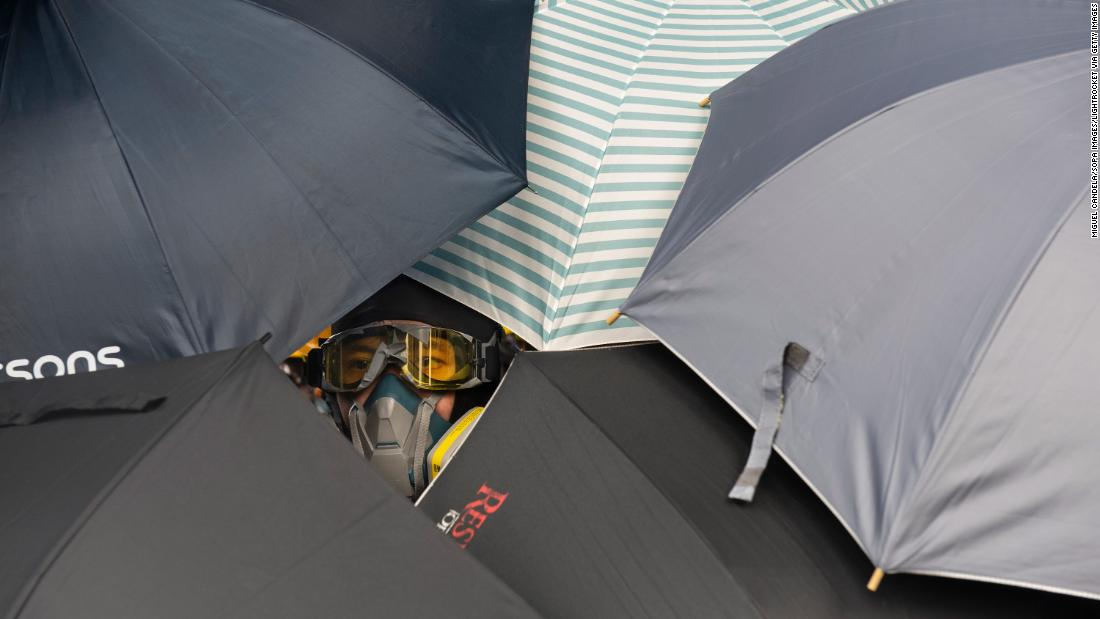A protester looks through umbrellas during the clashes with police on July 27.