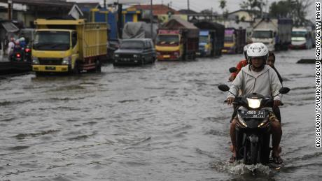 Vehículos en una inundación causada al elevar el nivel del mar en una carretera en Java Central, Indonesia, el 2 de febrero.