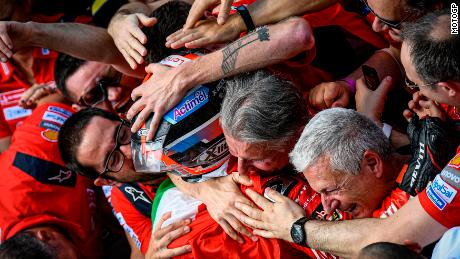 An exhausted, overjoyed Danilo Petrucci is embraced by his Ducati team in Parc Fermé.