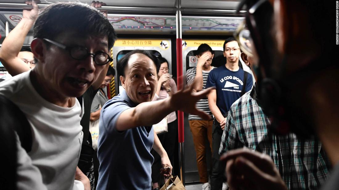 A train passenger gestures toward a protester, destra, who was preventing the doors of a train from closing on August 5. The protester was trying to disrupt Hong Kong's morning rush-hour commute.