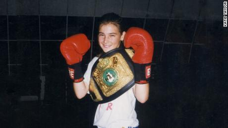 Katie Taylor with boxing gloves and a belt.