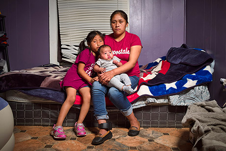 Isabella Gregorio Alonzo, 27, poses for a portrait with her daughters Juana, 7, and Angelina, 3 months, in the home she shares with other immigrants in Forest, Mississippi. Both Gregorio and her husband were detained. She was released with an ankle monitor, which can be seen on her right leg.