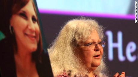 Susan Bro speaks next to a photo of Heather Heyer during a memorial for her daughter in 2017.