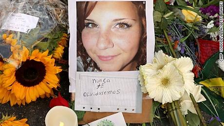 Flowers, candles and  messages surround a photograph of Heather Heyer on the spot where she was killed in August 2017.