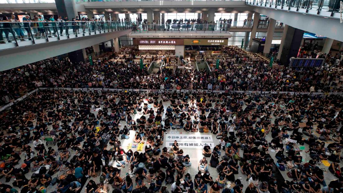 Protesters display banners during a sit-in rally at the airport's arrival hall on Monday, August 12.