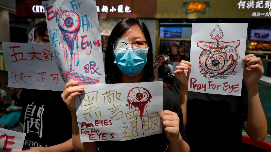 "People hold signs during <a href=""https://www.cnn.com/2019/08/12/asia/hong-kong-police-airport-intl-hnk/index.html"" target=""_blank"">airport protests</a> on August 12. The signs reference the woman who was allegedly shot in the eye with a beanbag round during clashes between protesters and police."