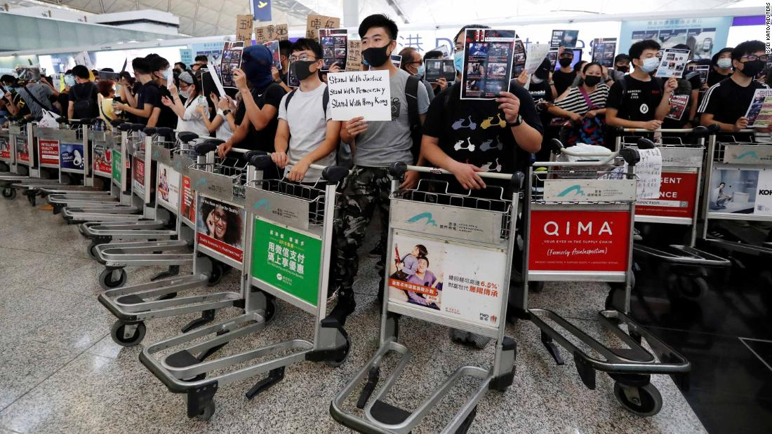 Anti-government protesters stand at a barricade made of luggage trolleys during a demonstration at the airport on August 13.