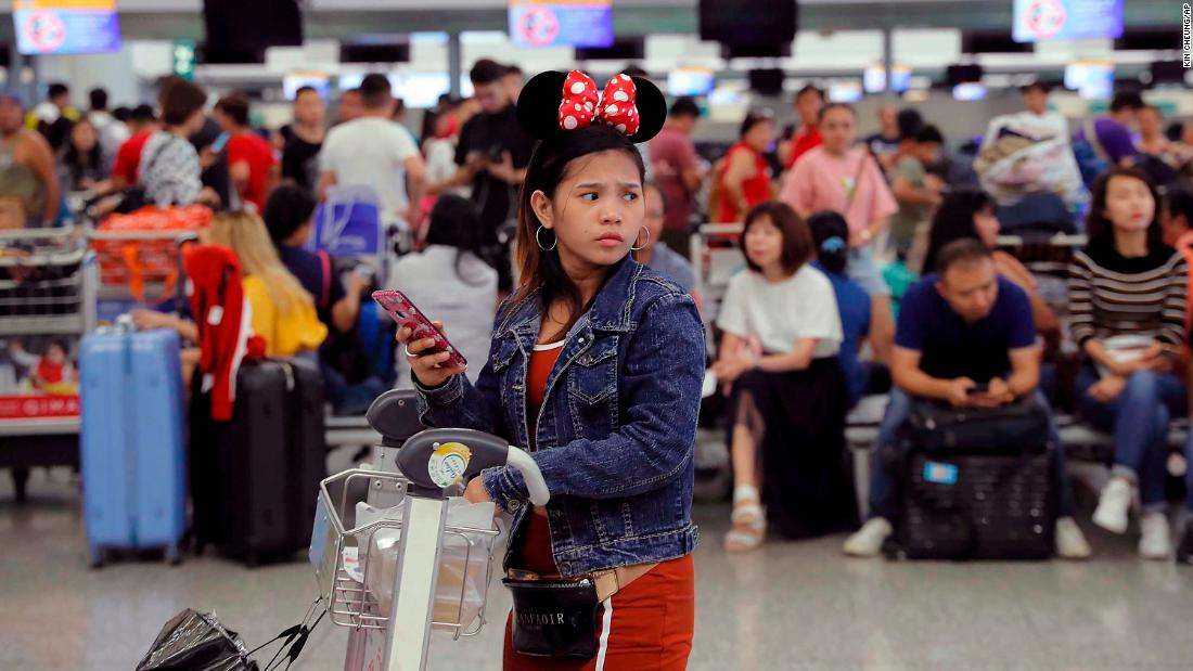A woman wearing Minnie Mouse headgear looks on as stranded travelers gather near closed check-in counters on August 13.