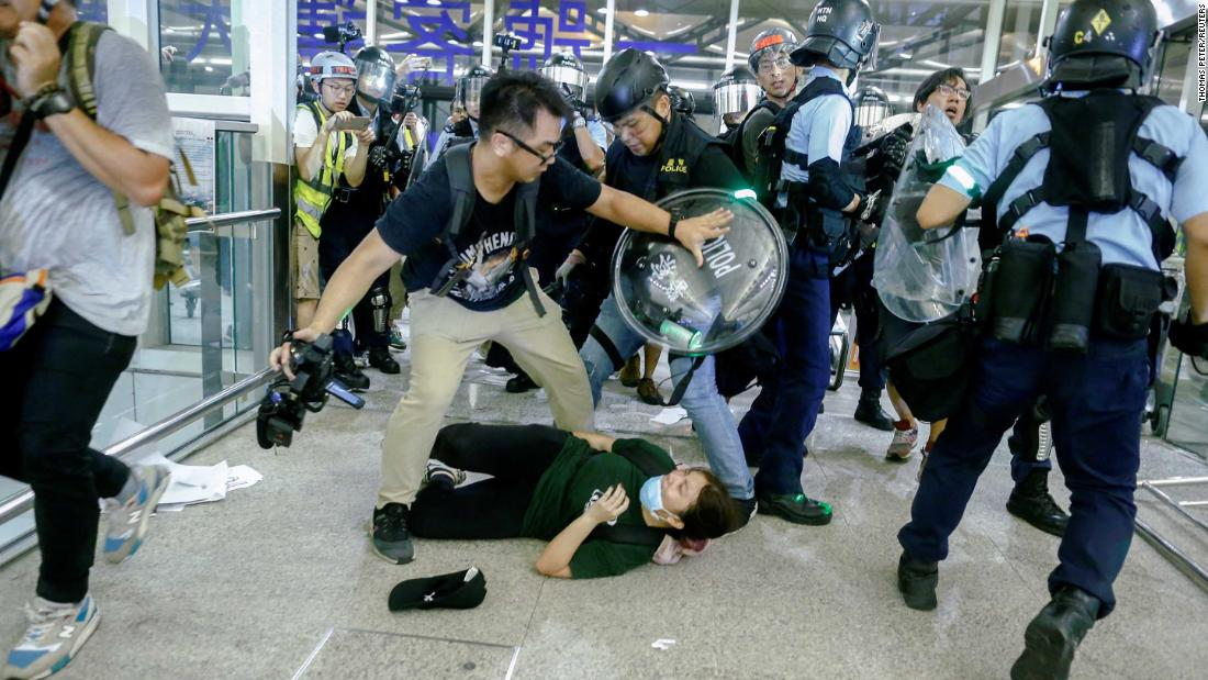 "Police and protesters clash at the airport on August 13. The violence came after Hong Kong's Airport Authority announced that all check-in services would be suspended for another night because of terminal operations being ""seriously disrupted."""