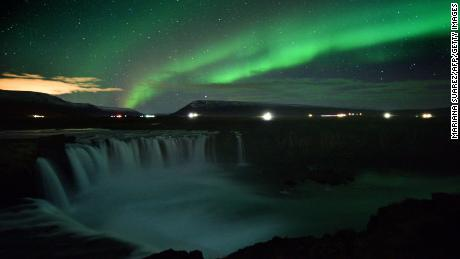 The northern lights over a waterfall in Iceland.