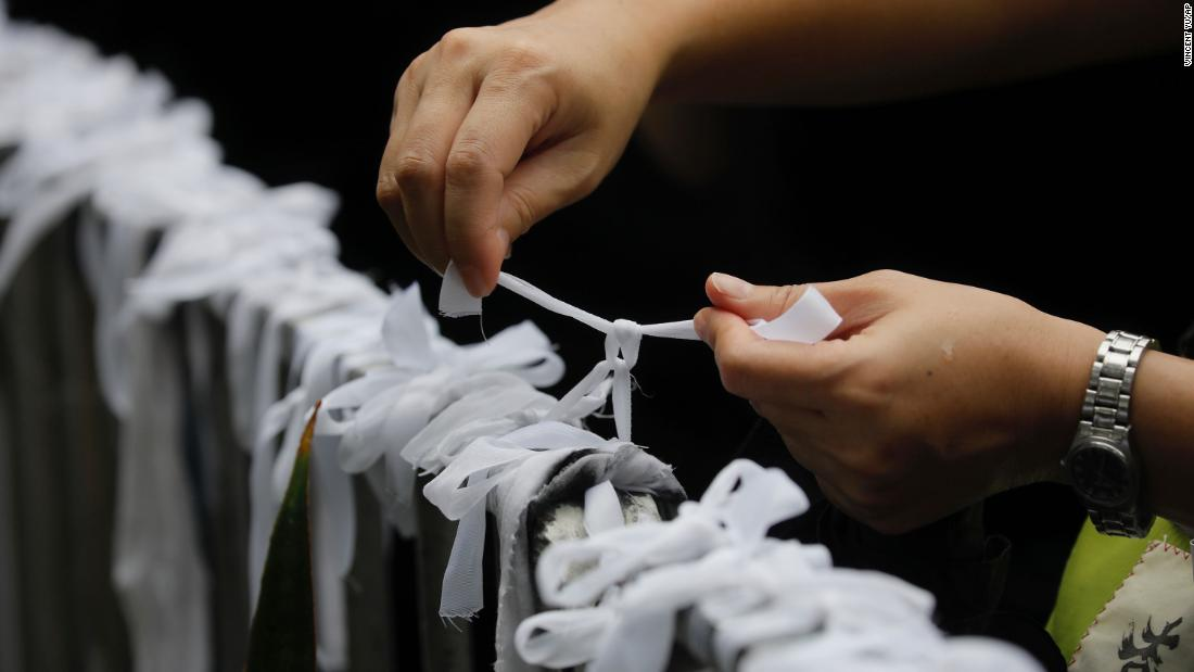 A protester ties a white ribbon, symbolizing the pure intentions of young protesters, during a march organized by teachers in Hong Kong on August 17.