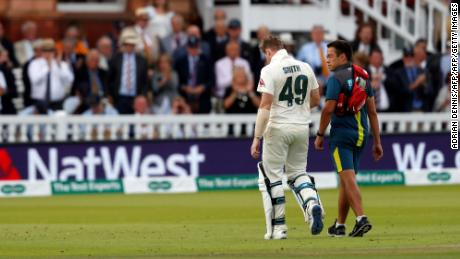 Smith leaves the pitch after being hit in the neck by Jofra Archer.