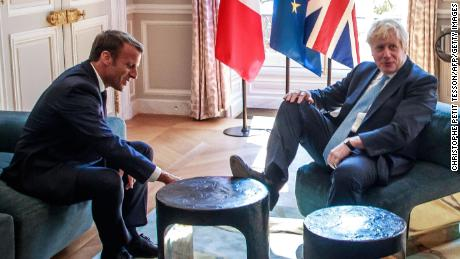 Boris Johnson places his foot on a table during a meeting with French President Emmanuel Macron at the Elysee Palace in Paris on August 22, 2019.
