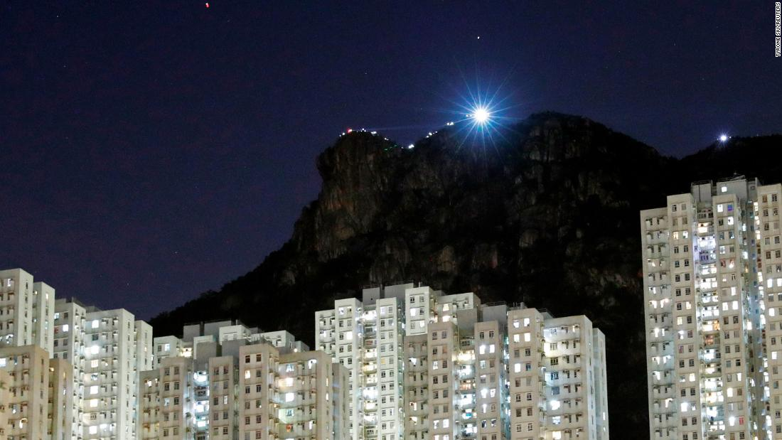 Protesters shine light from their cell phones as they form a human chain on top of the iconic Lion Rock at Wong Tai Sin.