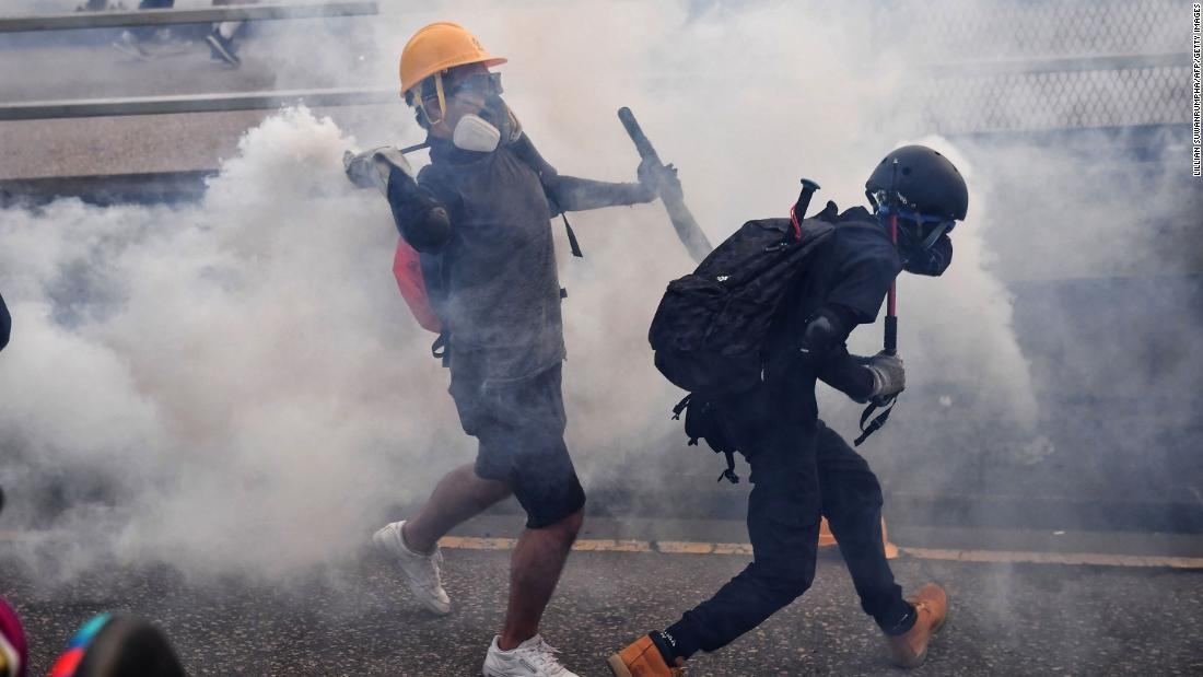 A protester throws back a tear-gas canister during clashes at Kowloon Bay on August 24.
