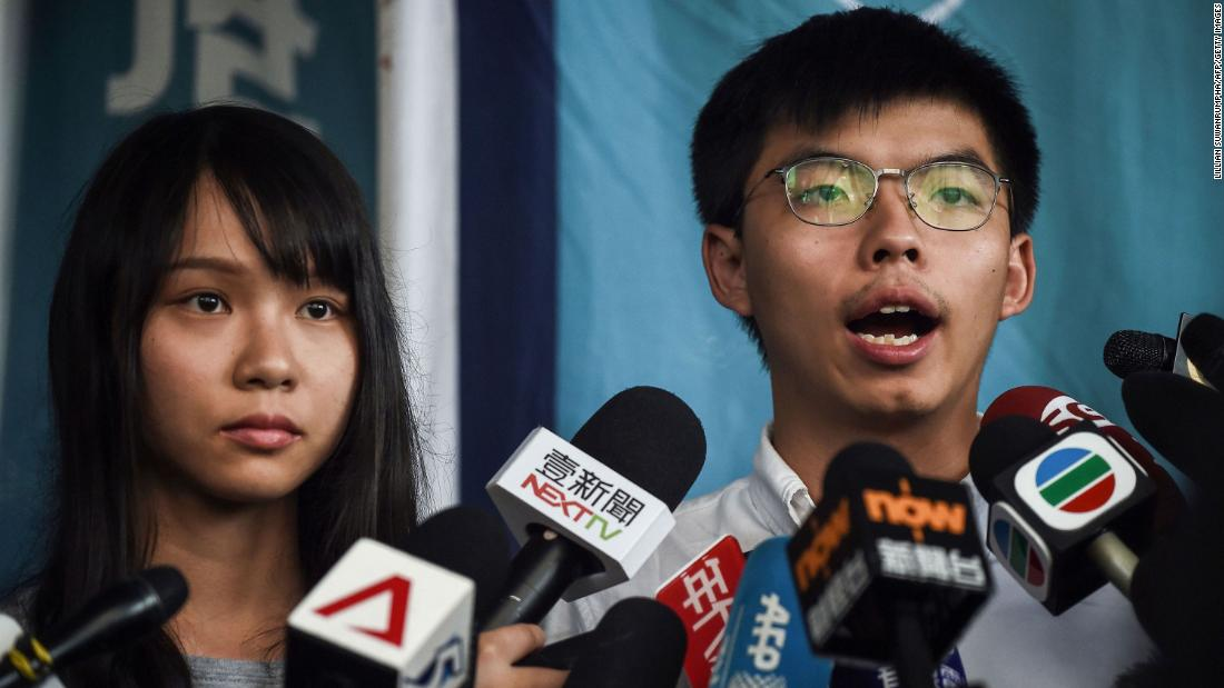 Pro-democracy activists Agnes Chow, left, and Joshua Wong, right, speak to the media after they were released on bail at the Eastern Magistrates Courts on August 30. The prominent democracy activists were arrested earlier the same day in a dragnet across Hong Kong.
