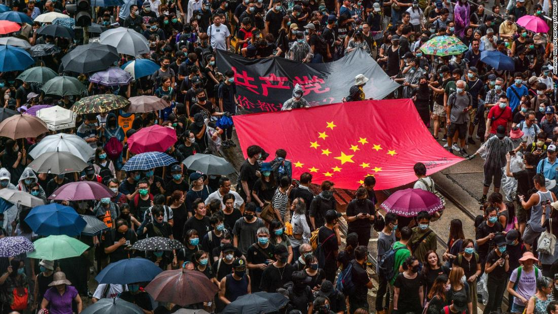 Protesters march with a banner that uses the stars of the Chinese national flag reconfigured to depict a Nazi swastika in the Central district of Hong Kong on August 31.