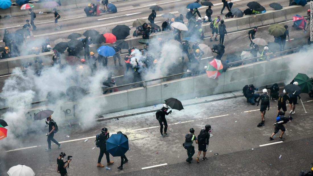 An overhead view showing protesters reacting after police fired tear gas in Hong Kong Saturday.