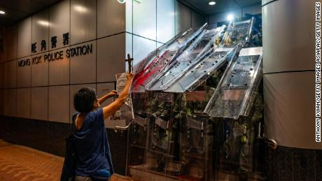 A woman holds a cross in front of the Mongkok Police Station as riot police holding shields stand guard during a standoff with protesters after an anti-government rally in on September 1, 2019, in Hong Kong.